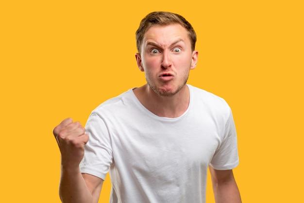 Retrato de homem zangado. gesto de advertência. cara irritado, ameaçando com o punho isolado em fundo laranja.