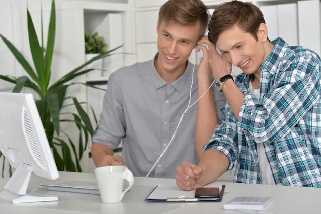 Retrato de homens bonitos com computador e telefone juntos