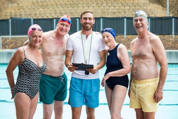 Retrato de idosos com instrutor em pé à beira da piscina