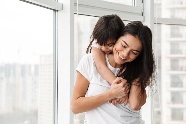Retrato de incrível família mãe e filha expressando amor e ternura, enquanto abraçava em casa perto de grandes janelas
