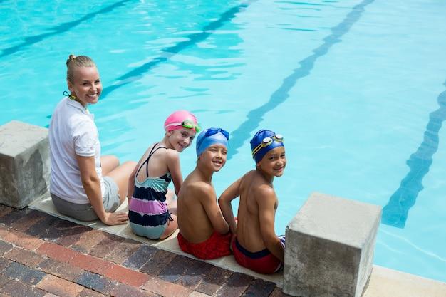 Retrato de instrutor de natação alegre e alunos ao lado da piscina