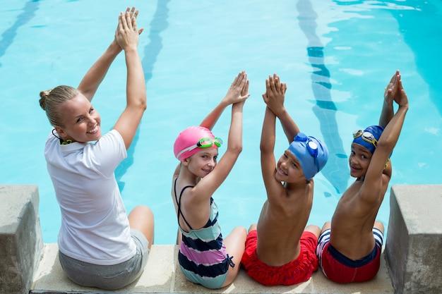 Retrato de instrutor de natação com alunos à beira da piscina