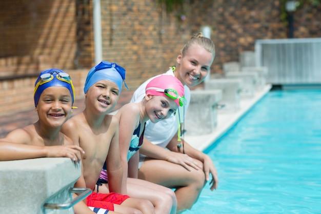 Retrato de instrutor de natação com alunos sentados à beira da piscina