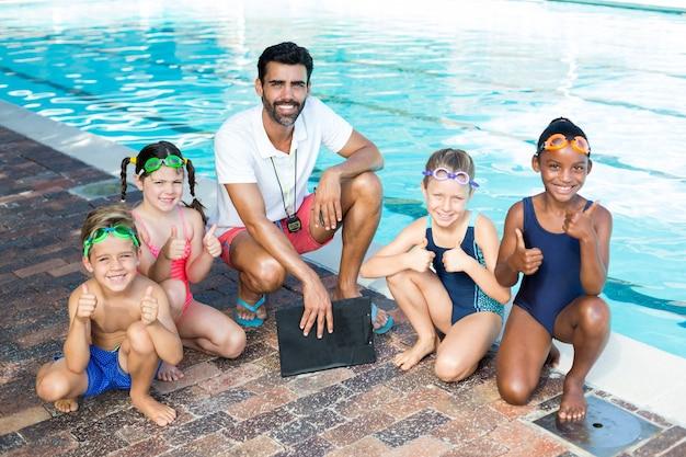 Retrato de instrutor de natação com crianças à beira da piscina