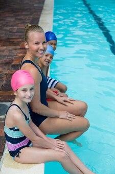 Retrato de instrutora de natação com alunos sentados à beira da piscina