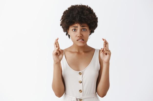 Retrato de intensa preocupação encantadora de pele escura com penteado afro, mordendo o lábio nervosamente, franzindo a testa e olhando ansiosamente enquanto cruza os dedos esperançosamente