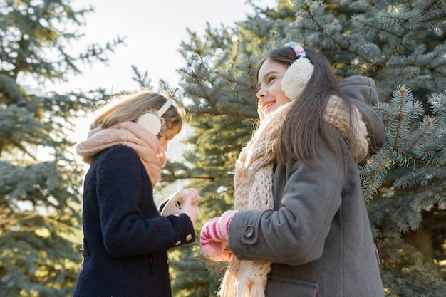 Retrato de inverno ao ar livre de duas meninas perto de árvore de natal.
