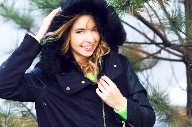 Retrato de inverno ao ar livre, estilo de vida, de uma menina sorridente muito brincalhão se passando perto de abeto, vestindo parka da moda