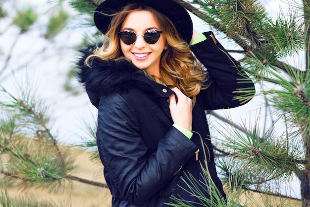 Retrato de inverno ao ar livre, estilo de vida, de uma menina sorridente muito brincalhona se passando perto de abeto, usando chapéu retrô óculos de sol vintage e parca da moda.