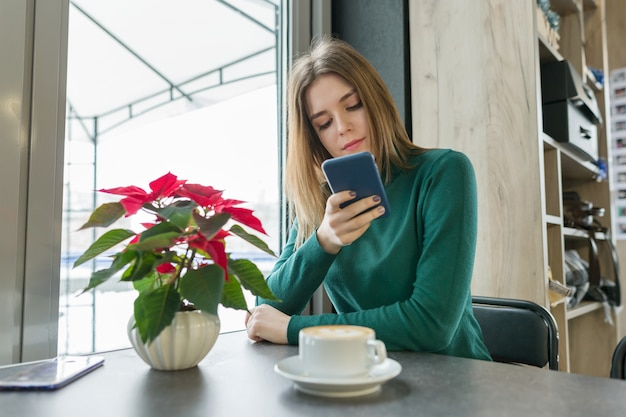 Retrato de inverno da linda jovem sentado no café