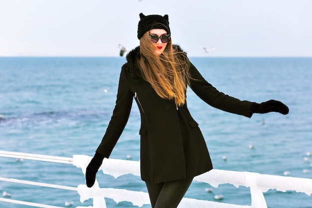 Retrato de inverno da moda da mulher loira elegante, aproveite o tempo de neve fria no mar, gelo e vento, casaco preto, chapéu engraçado, cabelos longos, humor sensual, viajar sozinho, moda de inverno.