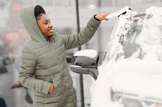 Retrato de inverno da mulher africana limpando a neve de um carro. mulher com uma jaqueta verde.