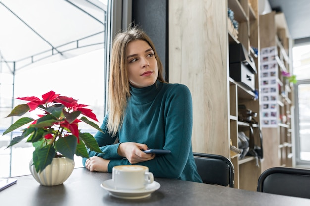 Retrato de inverno da mulher sentada no café com uma xícara de café