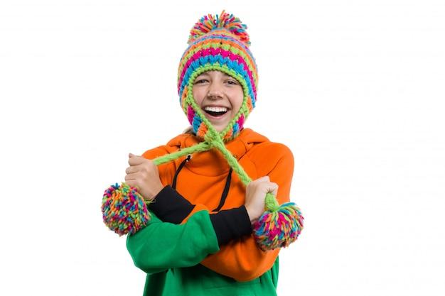 Retrato de inverno de adolescente engraçado no chapéu de malha