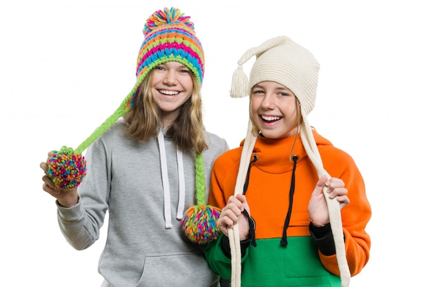 Retrato de inverno de duas meninas sorridentes felizes em chapéus de malha