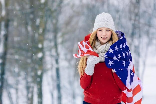 Retrato de inverno de jovem adolescente com bandeira eua. beleza alegre modelo menina rindo e se divertindo em winter park
