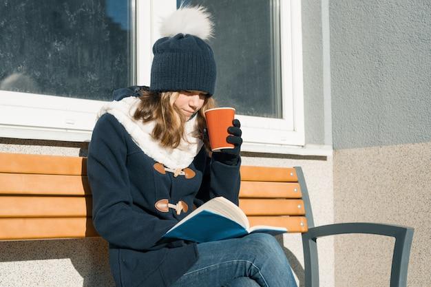 Retrato de inverno de jovem adolescente com copo de bebida quente e livro.