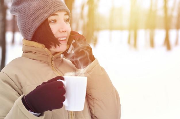 Retrato de inverno de jovem com smartphone e xícara de café