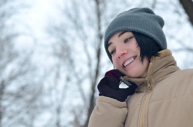 Retrato de inverno de jovem com smartphone