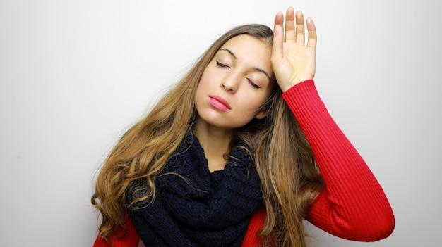 Retrato de inverno de mulher com dor de cabeça contra um fundo branco