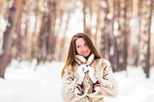 Retrato de inverno de mulher jovem e bonita com casaco de pele. conceito de moda neve inverno beleza.