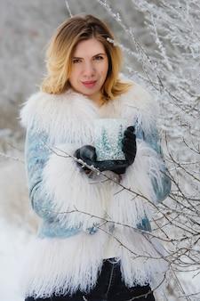 Retrato de inverno de mulher jovem sorridente no bosque nevado.