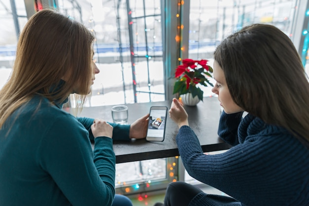 Retrato de inverno de mulheres jovens sentadas em um café