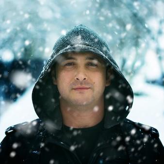 Retrato de inverno de um homem vestindo capuz na neve