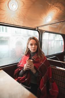 Retrato de inverno de uma jovem, coberta com um cobertor, sentada com uma xícara de café perto da janela e olhando para o lado