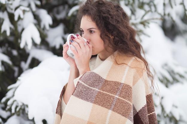 Retrato de inverno de uma jovem e linda mulher morena com malha de malha coberta de neve