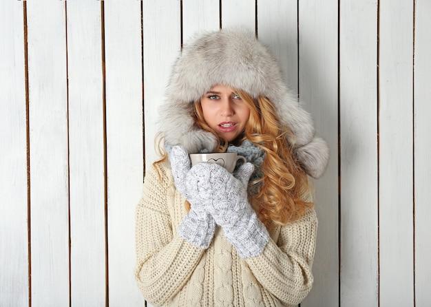 Retrato de inverno de uma jovem loira bonita em suas roupas quentes de malha, com um copo de bebida quente