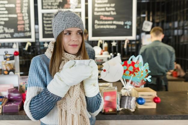 Retrato de inverno de uma jovem mulher bonita com uma xícara de café.