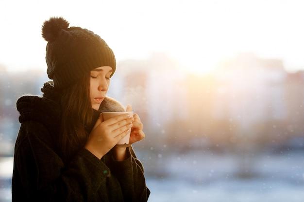 Retrato de inverno de uma menina com um copo de bebida quente nas mãos dela.