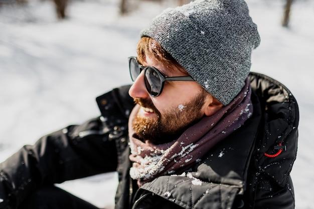 Retrato de inverno do homem moderno com barba e chapéu cinza relaxando no parque ensolarado com flocos de neve nas roupas