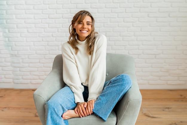 Retrato de inverno indooor de uma linda mulher de suéter aconchegante, sentado no sofá moderno em casa.
