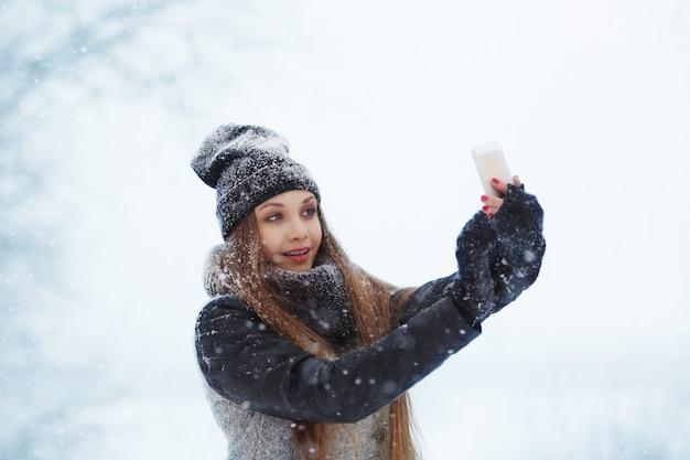 Retrato de inverno jovem. beleza alegre modelo menina rindo e se divertindo com o telemóvel