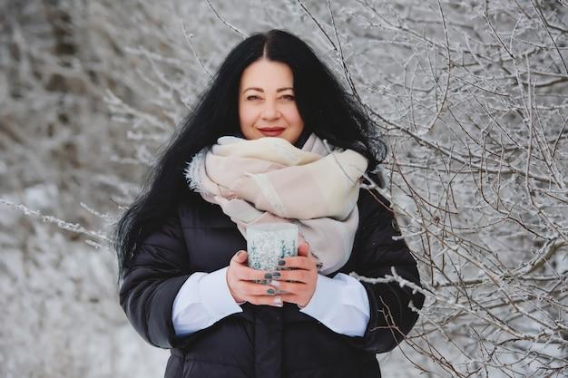 Retrato de inverno sorridente jovem morena em bosque nevado.