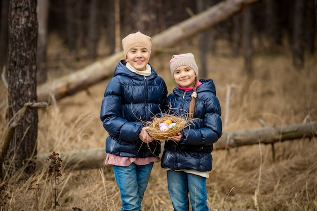 Retrato de irmã feliz posando com uma cesta de páscoa com ovos