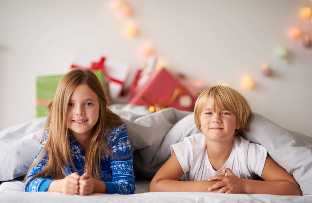 Retrato de irmãos felizes na cama no natal