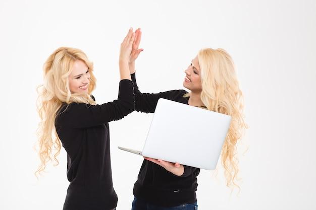 Retrato de irmãs gêmeas felizes com computador laptop comemorando seu sucesso isolado em um fundo branco