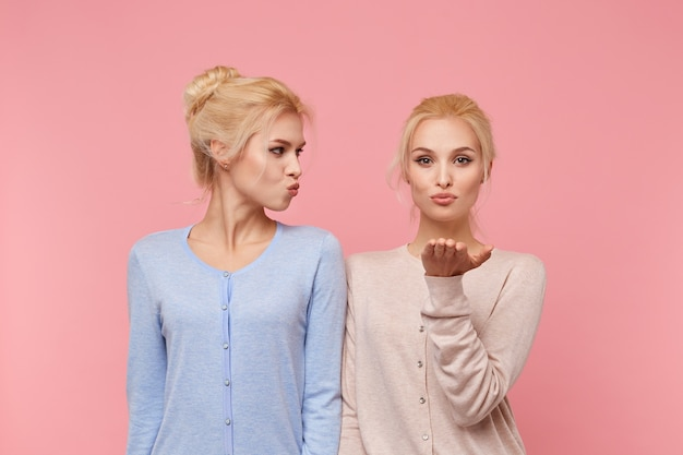 Retrato de irmãs gêmeas jovens loiras atraentes, mandar beijos no ar, expressar amor a alguém à distância, fica sobre fundo rosa.
