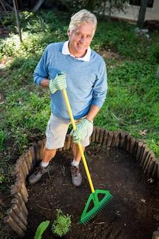Retrato de jardineiro feliz usando ancinho no jardim