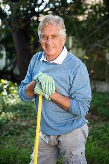 Retrato de jardineiro maduro com a ferramenta no jardim