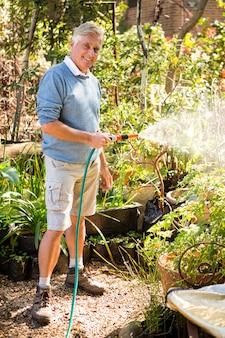 Retrato de jardineiro regar plantas de mangueira no jardim