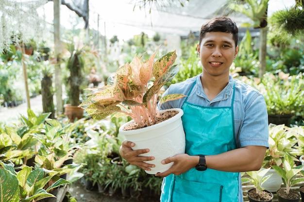 Retrato de jardineiro segurando plantas e flores