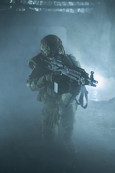 Retrato de jogador de airsoft em equipamento profissional com metralhadora em prédio em ruínas abandonado. soldado com armas em guerra em meio a fumaça e nevoeiro