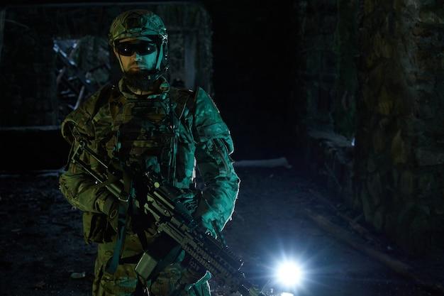Retrato de jogador de airsoft em equipamento profissional com metralhadora em prédio em ruínas abandonado. soldado com armas em guerra