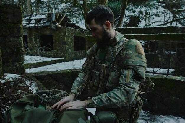 Retrato de jogador de airsoft em equipamento profissional com metralhadora na floresta. soldado com armas em guerra