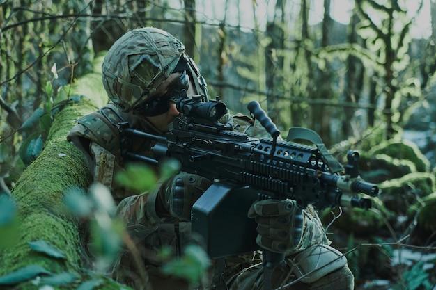 Retrato de jogador de airsoft em equipamento profissional em capacete visando a vítima com arma na floresta. soldado com armas em guerra