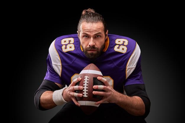 Retrato de jogador de futebol americano, segurando uma bola com as duas mãos